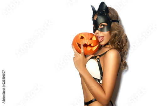 Obraz na płótnie Sexy girl with Halloween pumpkin in black leather cat mask on white isolated bac