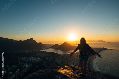 Brazil, Rio de Janeiro. Meeting the dawn on the hill Two brothers. View of the big city, lake, ocean, hills, mountains. Orange-blue colors Silhouette of a girl who looks at the city and sun.