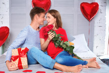 Happy Young Couple With Red Roses And Gift Box Sitting On Bed At Home