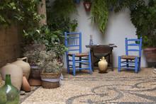 Precioso Patio Andaluz Con Plantas, Sillas De Color Azul, Mesa De Madera Y Vasijas Colocadas En Suelo De Piedra Con Mosaico. Córdoba, Andalucía, España. Viajes Y Turismo.
