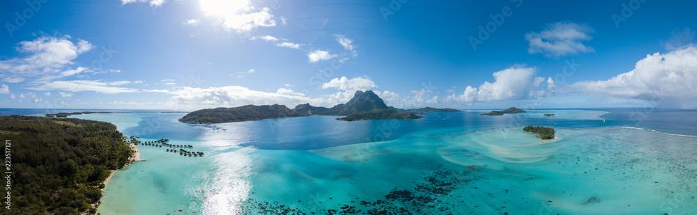 Fototapeta Panoramic aerial view of luxury overwater villas with palm trees, blue lagoon, white sandy beach and Otemanu mountain at Bora Bora island, Tahiti, French Polynesia (Bora Bora Aerial)