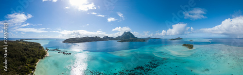 Ile Panoramic aerial view of luxury overwater villas with palm trees, blue lagoon, white sandy beach and Otemanu mountain at Bora Bora island, Tahiti, French Polynesia (Bora Bora Aerial)