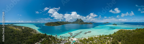 Panoramic aerial view of luxury overwater villas with palm trees, blue lagoon, white sandy beach and Otemanu mountain at Bora Bora island, Tahiti, French Polynesia (Bora Bora Aerial)