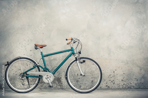 Photo Stands Bicycle Retro bicycle with aged brown leather saddle from circa 90s front concrete wall background. Vintage old style filtered photo