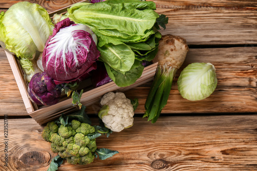 Crate with different types of cabbage on wooden background Canvas Print