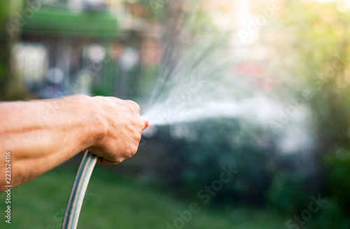 Fotografia Man watering flowers with a hose