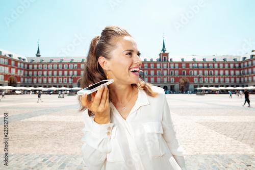 Naklejka premium szczęśliwa turystyczna kobieta słuchając audioprzewodnika na smartfonie