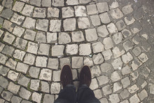 POV Shot Of A Man In Brown Shoes Standing On The Pavement