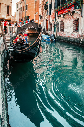 Traditional gondola with gondolier and tourists on narrow canal in Venice, Italy