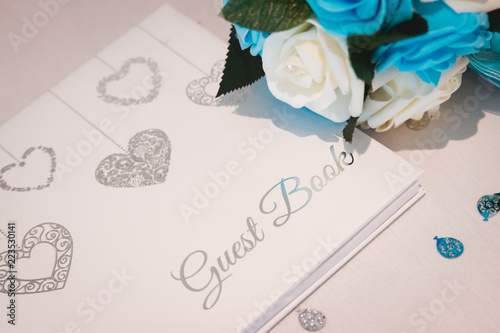 Wedding guest book laid on white silk and surrounded by flower petals Canvas Print