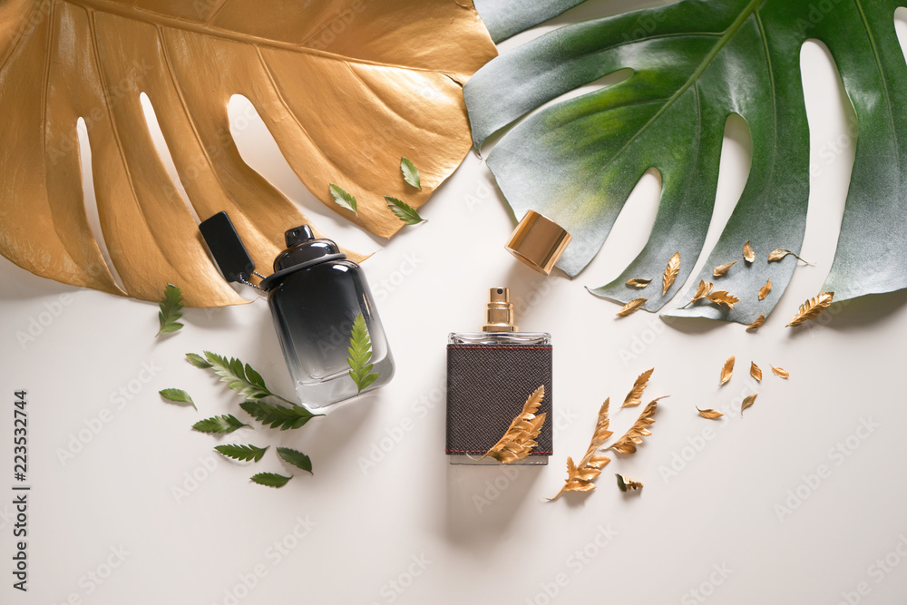 Fototapety, obrazy: Bottles with perfumes and tropical leaves on light background