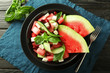 Plate with delicious watermelon salad on wooden table