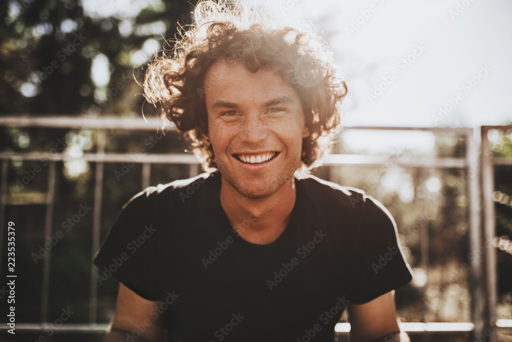 Fototapeta Outdoor closeup portrait of handsome freckled smiling male with curly hair, posing for social advertisement, in the city street on sunset sunlight with copy space for your promotional information