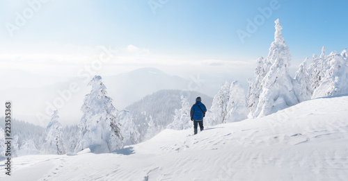 Alone tourist with a backpack in the high mountains in winter time. Travel concept