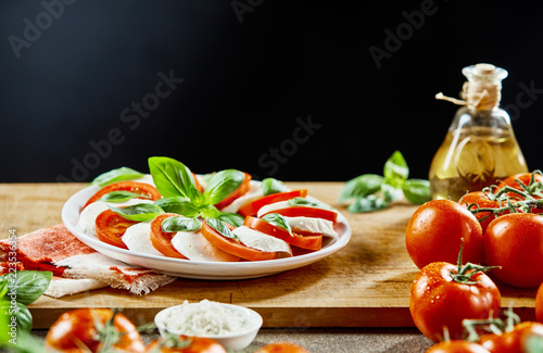Tomatoes, cheese and basil on wooden board