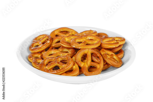 Fotografía  Snack, cookies, salted biscuit, brezel, bretzel to beer in front of alcohol on plate, white isolated background Side view