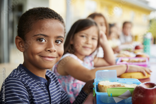 Young boy and girl at school lunch table smiling to camera Canvas Print