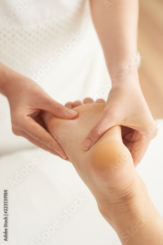 Close-up shot of hand rubbing foot of female client while
