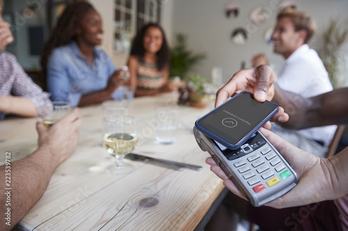 Fotografie, Obraz  Close Up Of Customer In Restaurant Paying Bill With Contactless Phone App
