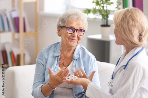 Fotografia  Doctor giving medicine to senior woman at home