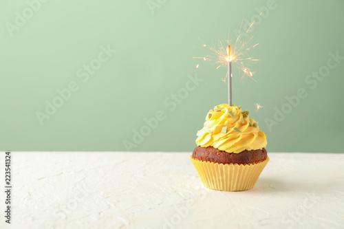 Photo  Delicious birthday cupcake with sparkler on white table