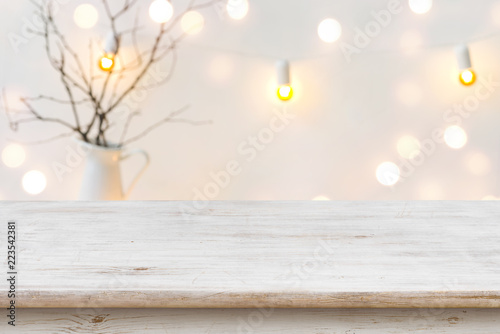 Wooden table in front of blurred abstract winter holiday background