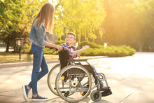 Boy In Wheelchair And His Sister Outdoors