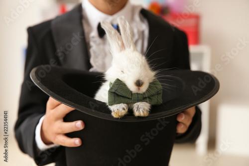 Cute little magician holding hat with rabbit indoors, closeup Wallpaper Mural