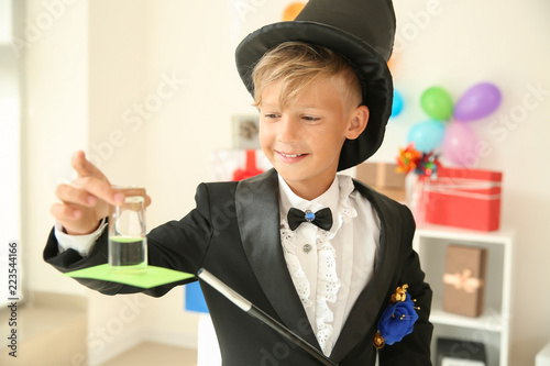 Photo Cute little magician showing trick indoors