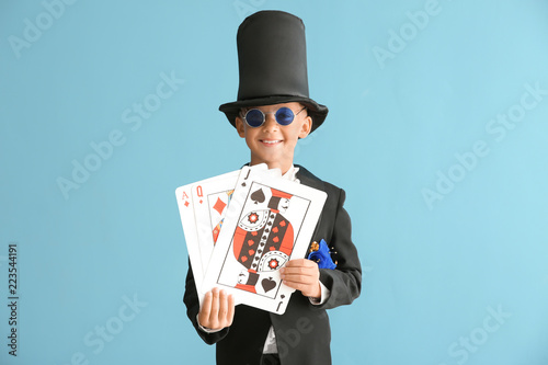 Fotografie, Obraz Cute little magician with cards on color background