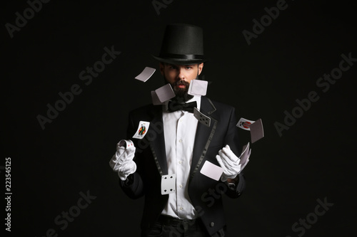 Magician showing tricks with cards on dark background Wallpaper Mural