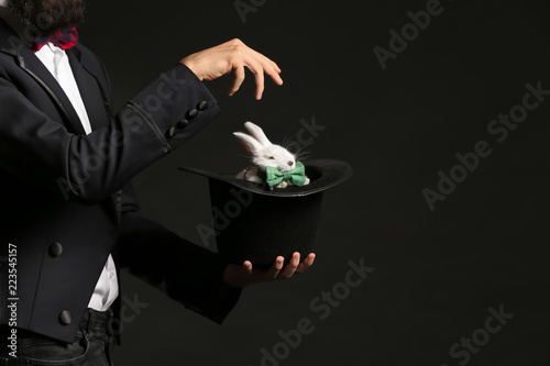 Foto Magician holding hat with rabbit on dark background