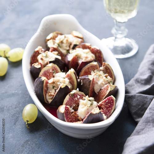 Figs baked with goat cheese, walnuts, honey and thyme on dark blue background.