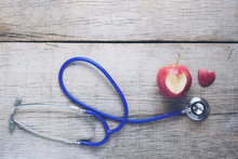 Stethoscope And Apple On Wood Background. Concept Of Love For Health. Selective Focus