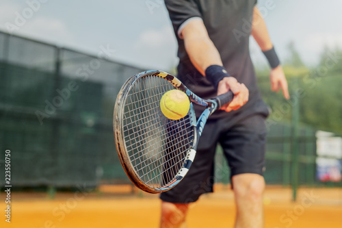 Photo Close up of man playing tennis and beating the ball with a racket