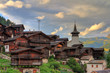 Leinwanddruck Bild - Beautiful cityscape of the alpine village Grimentz, Switzerland, with traditional wooden houses and church tower in summer