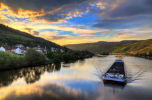 Beautiful Vibrant Sunset View Of The River Moselle At The Small Wine Growing Town Zell (an Der Mosel) With Hills Full Of Grape Vines With A Barge On The River