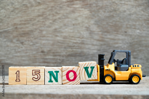 Vászonkép  Toy forklift hold block V to complete word 15nov on wood background (Concept for