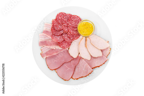 Fotografiet Cold appetizer assorted meat, slices of salami, ham, chicken, carbonate, brisket, boiled pork, fillets, mustard sauce, before alcohol, on plate, white isolated background view from above