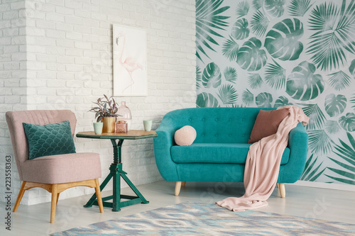 Real photo of turquoise couch and pastel pink armchair standing in bright living room interior with flamingo poster on brick wall and leafy wallpaper