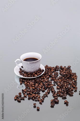 White cup with coffee. Coffee beans. Reflection in the mirror.