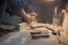 Handmade Concept. Women's Hands Do The Product Of Wood. Wood Workshop With A Tool And A Lamp