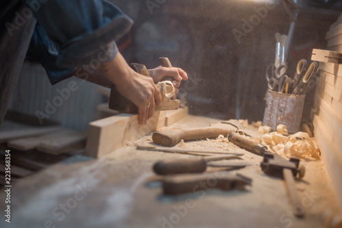 Obraz Handmade concept. Women's hands do the product of wood. Wood workshop with a tool and a lamp - fototapety do salonu