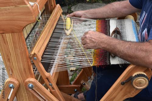 Fotografie, Obraz  Hands of middle-aged man - craftsman weaver - working on wooden handloom, Etara
