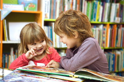 Fotografie, Obraz Cute two little kids, brother and sister  reading a book together in library