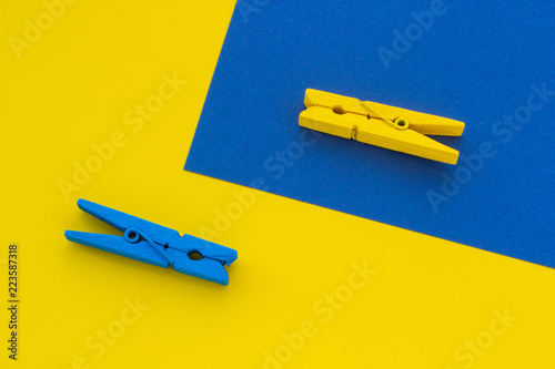 Fotografie, Obraz  Blue and yellow clothespins on the background
