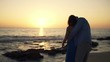 Young couple hugging and kissing during sunset on beach