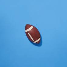 Classic NFL Football Leather Pigskin Worn Football Top Down View On Blue Background