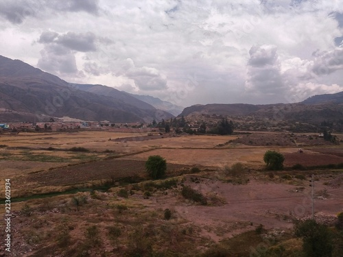 yellow crops and trees, mountains at medium distance, sky with white clouds and black background, in the vicinity of the city of Cusco, Peru.