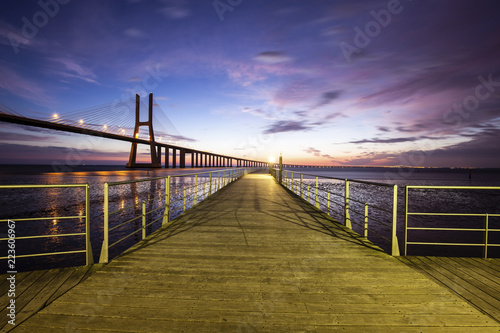 Diminishing perspective of pier over Tagus River against sky during sunrise